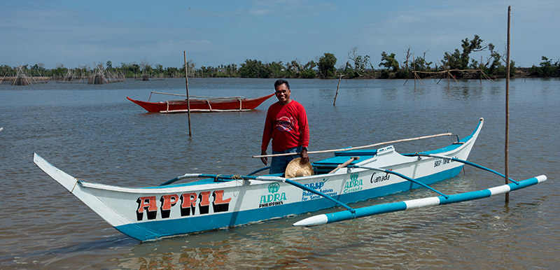 Man in the Philippines stand by his new fishing boat that he was able to build with the help of ADRA.